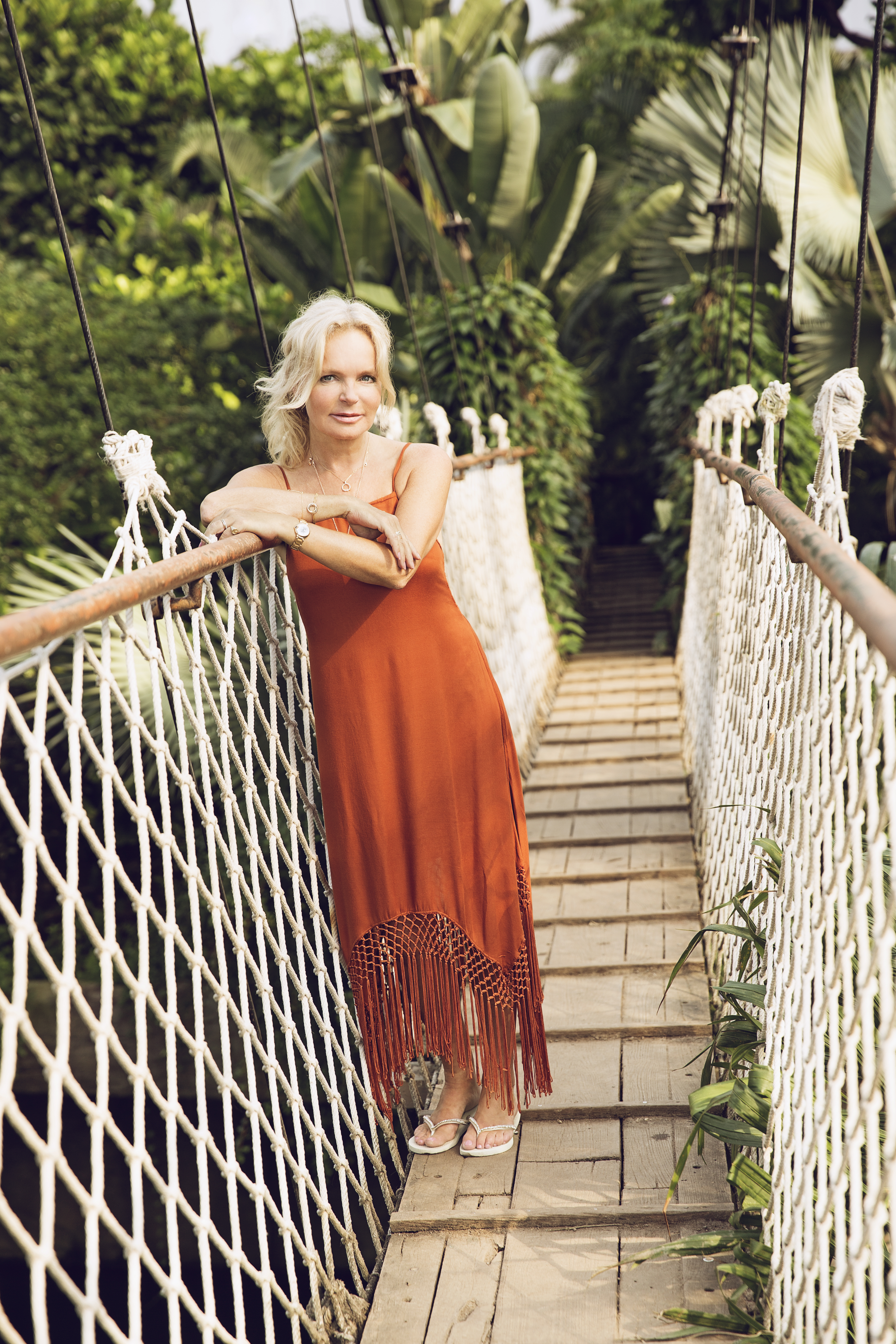 Photo of Author Lucinda Riley wearing a rust-orange sundress, standing on a walkway in lush green scenery. The author is leaning on the railing with arms crossed.